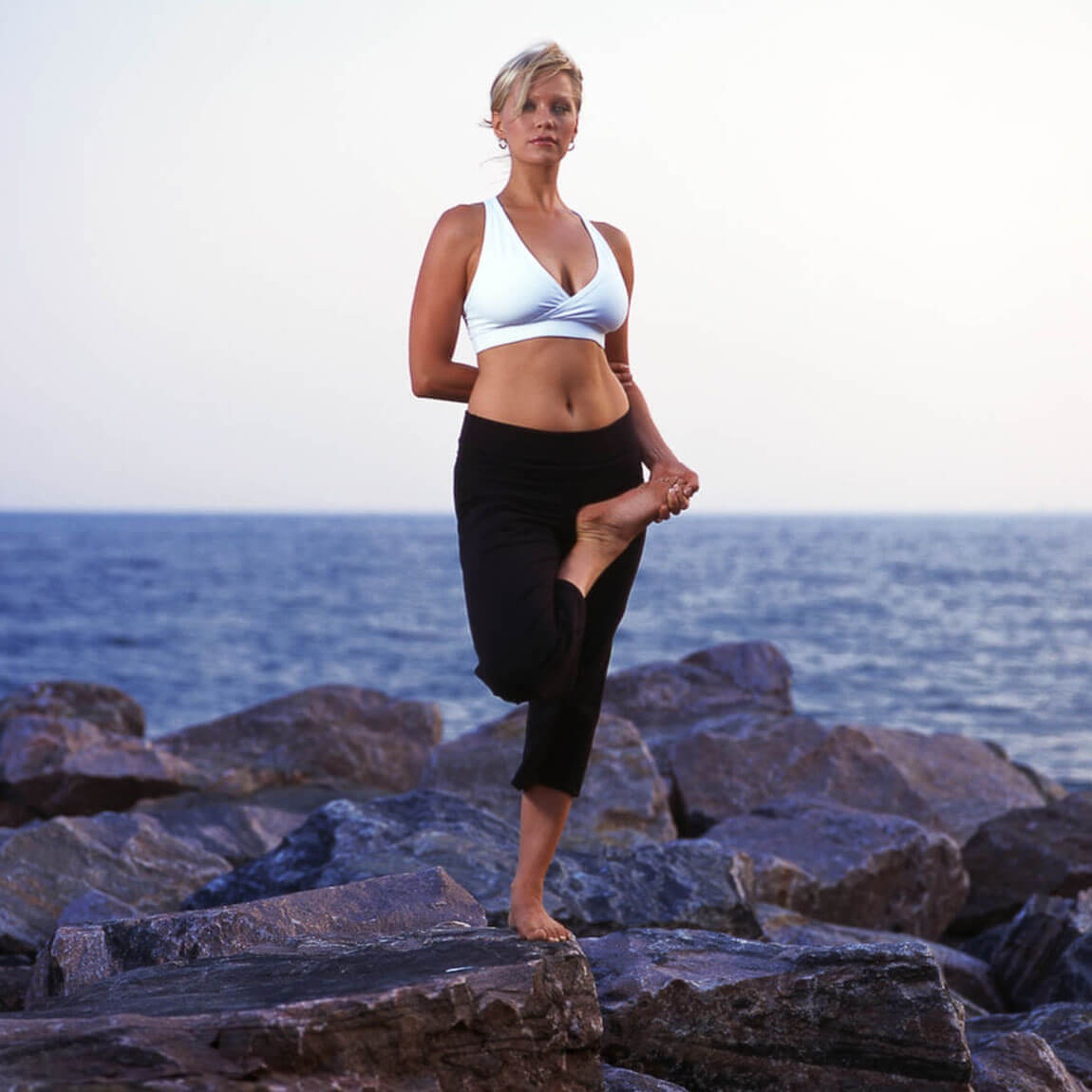 woman in a yoga pose by the sea